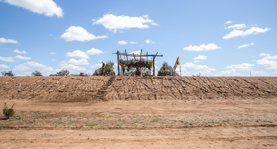 An image showing the Wangan and Jagalingou from a distance, on top of a mound.