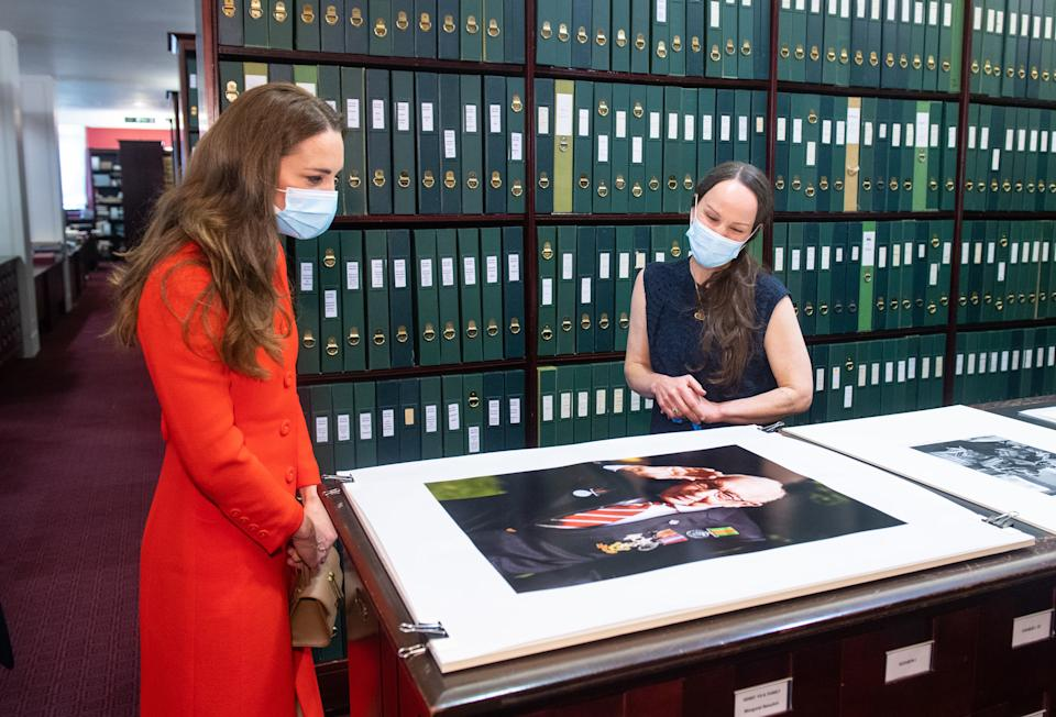 LONDON, ENGLAND - MAY 07: Catherine, Duchess of Cambridge views a photo of Captain Tom Moore alongside Curator Magda Keaney during a visit to the archive in the National Portrait Gallery in central London to mark the publication of the 'Hold Still' book on May 7, 2021 in London, England. (Photo by Dominic Lipinski - WPA Pool/Getty Images)
