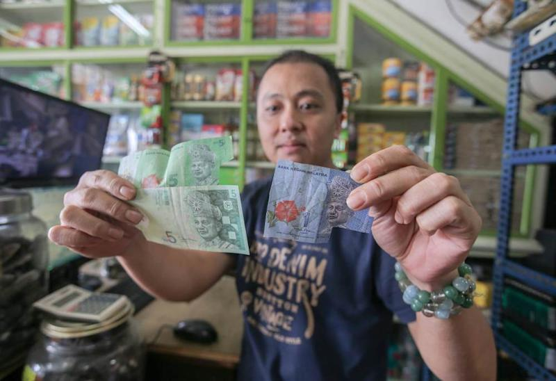 Sharikat Choy's owner Choy Chi Choong shows the damaged notes he received from customers.