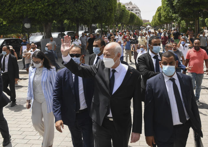 Tunisian President Kais Saied waves to bystanders as he stroll along the avenue Bourguiba in Tunis, Tunisia, Sunday, Aug. 1, 2021. President Kais Saied claimed on Sunday that some desperate youth are being paid to try to leave Tunisia illegally for Europe, saying the goal is to damage the country from within. (Slim Abid/Tunisian Presidency via AP)