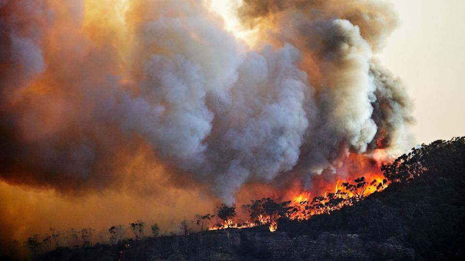Bushfire rages on clifftop due to climate change.