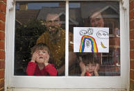 FILE - In this Saturday, April 4, 2020 file photo Amelie and her sister Camille watch from their front window as the lockdown enters it's third week along with their parents Victoria and Damian Kerr in Berkhamsted, England. (AP Photo/Elizabeth Dalziel, File)