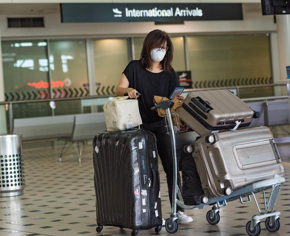 A woman wears a face mask as a precaution against the spread of Coronavirus at Brisbane Airport.
