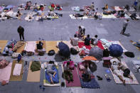 Migrant workers and their families rest in an exhibition hall after being evacuated from their workplaces in Hangzhou in eastern China's Zhejiang province Sunday, July 25, 2021. A typhoon blew heavy rain across the Shanghai region Monday, leaving roads and low-lying areas waterlogged and felling billboards and signs on its second landfall in eastern China. (Chinatopix via AP)