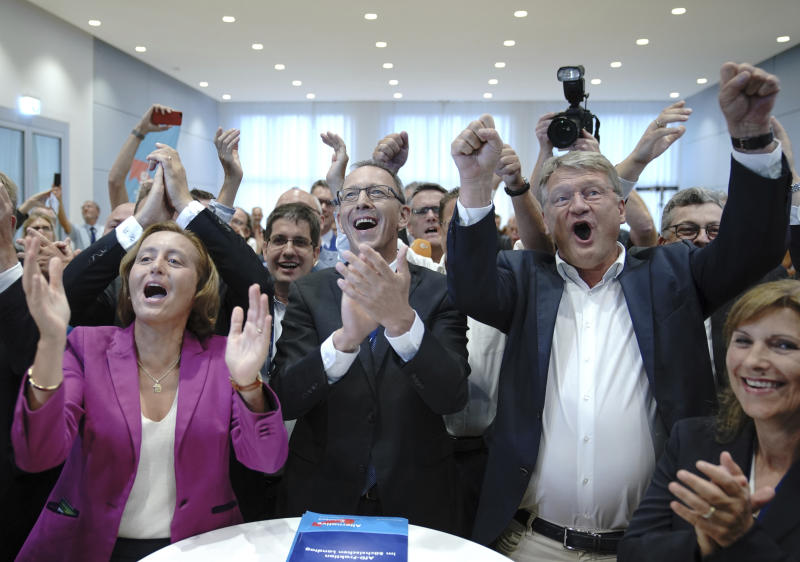 Chairman of right-wing party Alternative for Germany, AfD, Joerg Meuthen, second from right, top candidate Joerg Urban, center, top candidate for the Saxony state elections and board member Beatrix von Storch, left, react after first election results announced in Dresden, Germany, Sunday, Sept. 1, 2019. The citizens of the German states Saxony and Brandenburg elected their new parliament. (Michael Kappeler/dpa via AP)