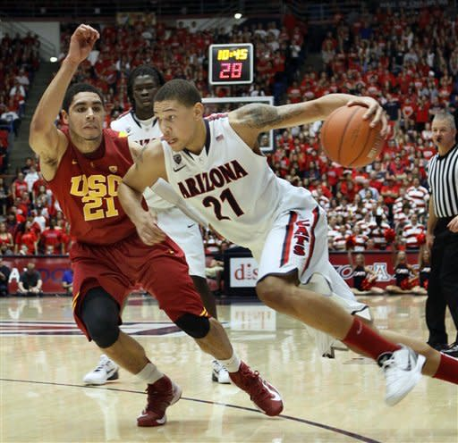 Arizona's Brandon Ashley, right, drives to the basket around Southern California's Aaron Fuller during the second half of an NCAA college basketball game at McKale Center in Tucson, Ariz., Saturday, Jan. 26, 2013. (AP Photo/Wily Low)