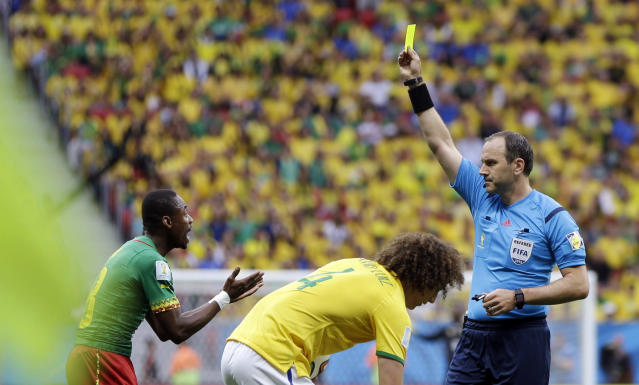 Cameroon's Eyong Enoh, left, is booked by referee Jonas Eriksson from Sweden during the group A World Cup soccer match between Cameroon and Brazil at the Estadio Nacional in Brasilia, Brazil, Monday, June 23, 2014. (AP Photo/Andre Penner)