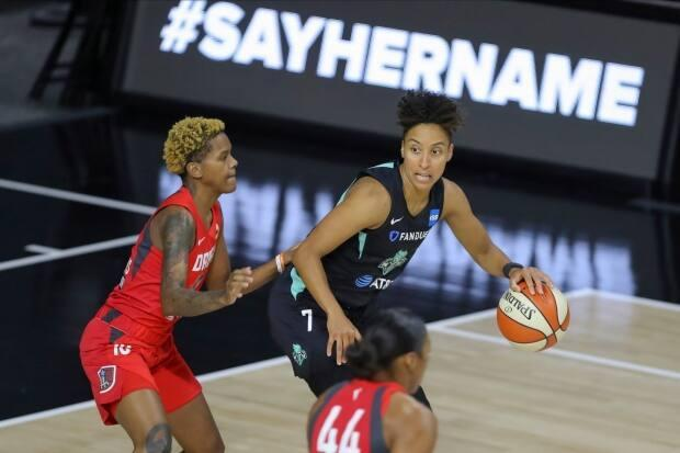 The Atlanta Dream's Courtney Williams, left, defends New York Liberty's Layshia Clarendon (7) during a game in front of a #SayHerName banner referencing Black female victims of police brutality. The Dream players were instrumental in helping defeat their former owner for a Senate seat in the 2020 election. denton, Fla. (AP Photo/Mike Carlson)