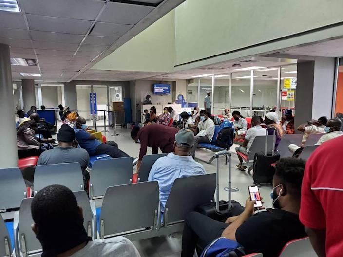 U.S.-bound travelers waiting inside a departure lounge at the Toussaint Louverture International Airport in Port-au-Prince Haiti, Tuesday, Jan. 26, 2021. The lounge is usually packed with travelers, but many were denied boarding because of new U.S. rules requiring a negative COVID-19 test to board.