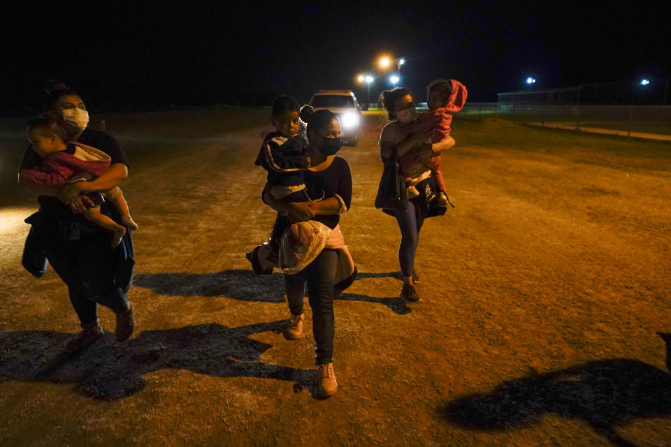 Migrant women carry children in the rain at an intake area after turning themselves in upon crossing the U.S.-Mexico border, late Tuesday, May 11, 2021, in La Joya, Texas. The U.S. government continues to report large numbers of migrants crossing the U.S.-Mexico border with an increase in adult crossers. But families and unaccompanied children are still arriving in dramatic numbers despite the weather changing in the Rio Grande Valley registering hotter days and nights. (AP Photo/Gregory Bull)