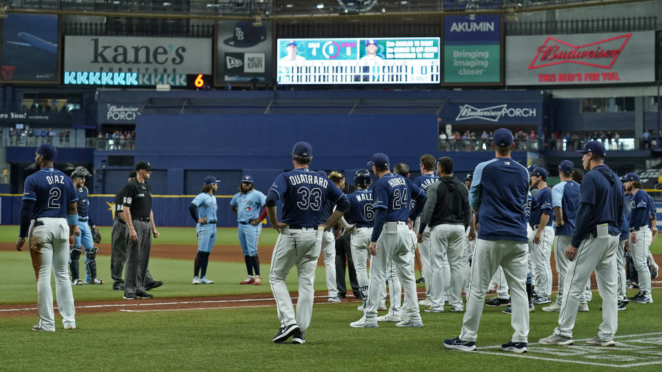 Tampa Bay Rays and Toronto Blue Jays players stand on the field after Blue Jays pitcher Ryan Borucki hit Rays' Kevin Kiermaier with a pitch during the eighth inning of a baseball game Wednesday, Sept. 22, 2021, in St. Petersburg, Fla. (AP Photo/Chris O'Meara)