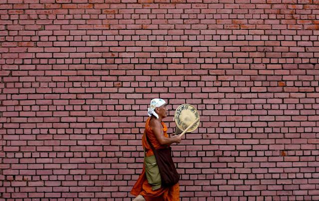 <p>A monk plays a traditional musical instrument as he walks along a street in the early morning in Colombo, Sri Lanka on May 16, 2017. (Photo: Dinuka Liyanawatte/Reuters) </p>