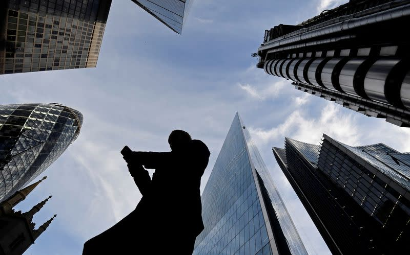 A worker looks at their phone as they walk past The Gherkin, Lloyds, and other office buildings in the City of London