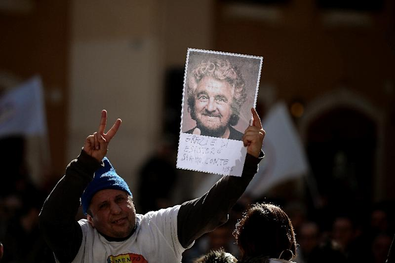 A supporter of anti-establishment party Five Star movement holds a portrait of its leader Beppe Grillo in front of the Montecitorio palace, the Italian Chamber of Deputies, in Rome, on February 15, 2014 (AFP Photo/Filippo Monteforte)