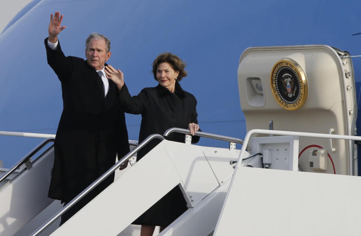 Former President George W. Bush waves to the crowd along with his wife, Laura Bush, after the flag-draped casket of former President George H.W. Bush was carried by a joint services military honor guard to an Air Force jet during a departure ceremony at Andrews Air Force Base, Md., Wednesday, Nov. 5, 2018. (AP Photo/Steve Helber)