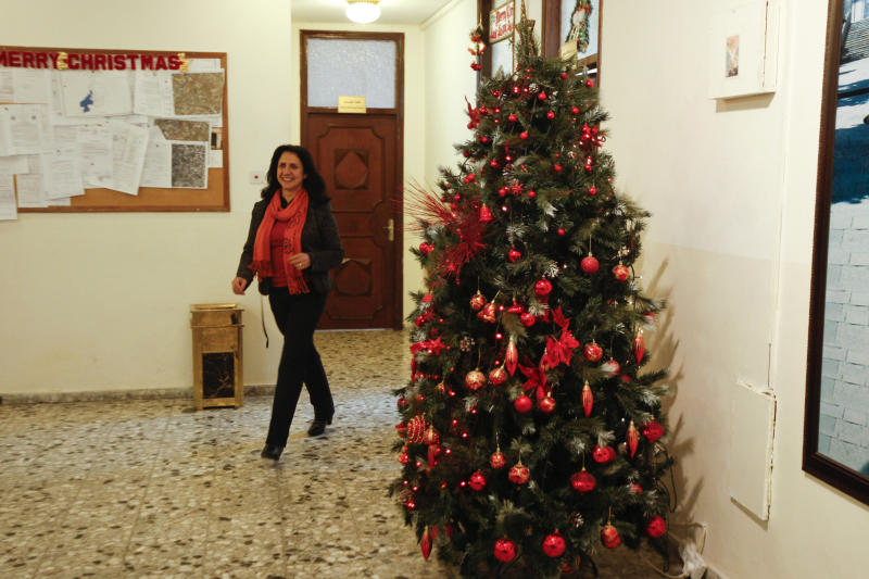 """In this photo taken on Monday, Dec 17, 2012, Bethlehem's first female mayor, Vera Baboun, walks out of her office in the West bank city of Bethlehem. Bethlehem's first female mayor, Vera Baboun, can't walk through the main square of the biblical town without being stopped by admirers.""""This is our new mayor, who is turning Bethlehem into one of the greatest cities in the world,"""" a tour guide hollered to a group of Christian tourists passing by the Church of the Nativity, built over the grotto where tradition says Jesus was born. After seven years of Islamist Hamas control of Bethlehem that drained the town of international aid funds, Baboun, a Christian, and her colleagues from the more moderate Fatah Party hope to turn things around, starting with the Christmas season. (AP Photo/Majdi Mohammed)"""