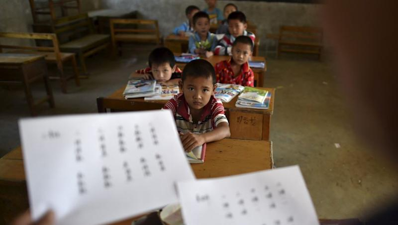 "Students look at their teacher holding papers of the new curriculum at a classroom of Dalu primary school in Gucheng township of Hefei, Anhui province, China, September 8, 2015. The school, opened in 2006 and has never acquired a legal license, may face a shutdown order from the government. There are currently over 160 students in the school, mostly ""leftover children"", whose parents left their hometown to earn a living, local media reported. Picture taken September 8, 2015. REUTERS/Stringer CHINA OUT. NO COMMERCIAL OR EDITORIAL SALES IN CHINA - RTS8MN"