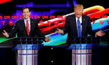 Republican U.S. presidential candidates Marco Rubio (L) and Donald Trump react to each other as they discuss an issue during the debate sponsored by CNN for the 2016 Republican U.S. presidential candidates in Houston, Texas, February 25, 2016. REUTERS/Mike Stone