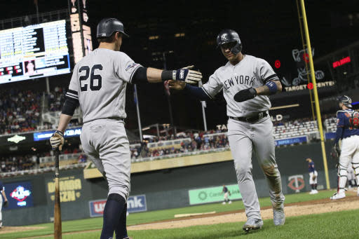 New York Yankees' Gleyber Torres celebrates with teammate DJ LeMahieu, left, after scoring on an RBI single by Didi Gregorius during the seventh inning in Game 3 of a baseball American League Division Series against the Minnesota Twins, Monday, Oct. 7, 2019, in Minneapolis. (AP Photo/Jim Mone)