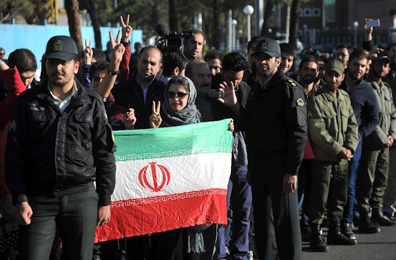 Iranians hold their national flag as they wait for Foreign Minister Mohammad Javad Zarif and the nuclear negotiating committee to arrive in Tehran on April 3, 2015 (AFP Photo/Borna Ghasemi)