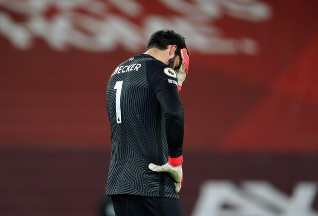 Liverpool goalkeeper Alisson Becker covers his face with his hand after making a mistake against Manchester City