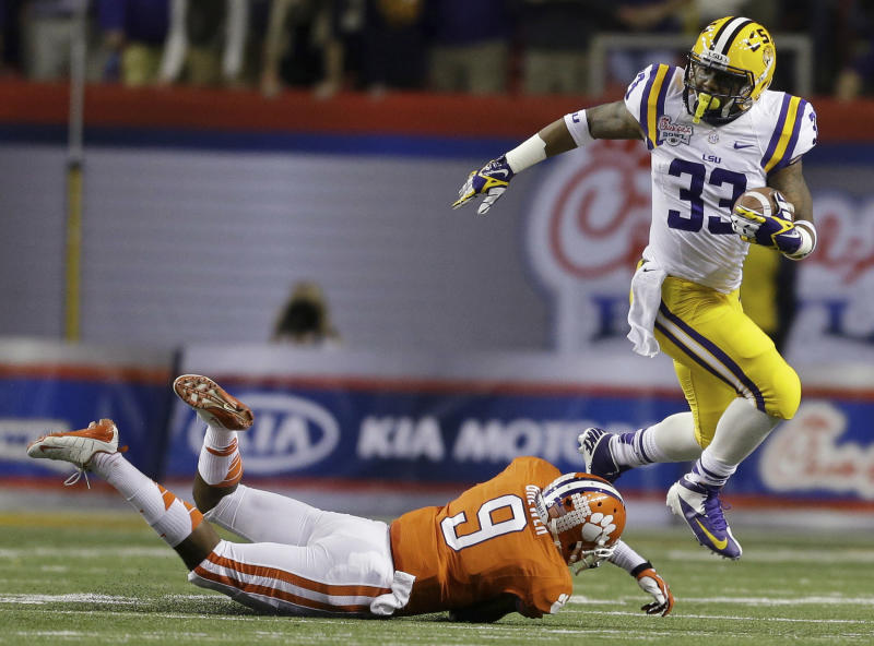 LSU running back Jeremy Hill (33) runs past Clemson defensive back Xavier Brewer (9) during the first half of the Chick-fil-A Bowl NCAA college football game, Monday, Dec. 31, 2012, in Atlanta. (AP Photo/David Goldman)