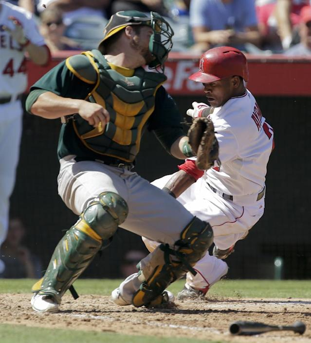 Los Angeles Angels' Erick Aybar, right, scores past Oakland Athletics catcher Stephen Vogt on a ball hit by Josh Hamilton during the fourth inning of a baseball game in Anaheim, Calif., Wednesday, Sept. 25, 2013. (AP Photo/Chris Carlson)