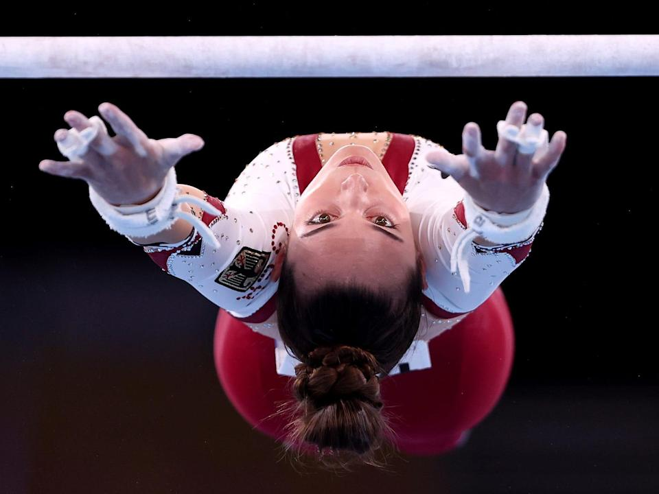 Pauline Schaefer-Betz of Team Germany reaches for the uneven bars, upside down.