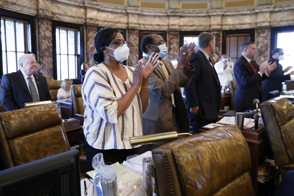 Senators stand and applaud after the body passed legislation to change the state flag, Sunday, June 28, 2020, at the Capitol in Jackson, Miss. Lawmakers in both chamber voted to surrender the Confederate battle emblem from their state flag. Republican Gov. Tate Reeves has said he will sign the bill. (AP Photo/Rogelio V. Solis)