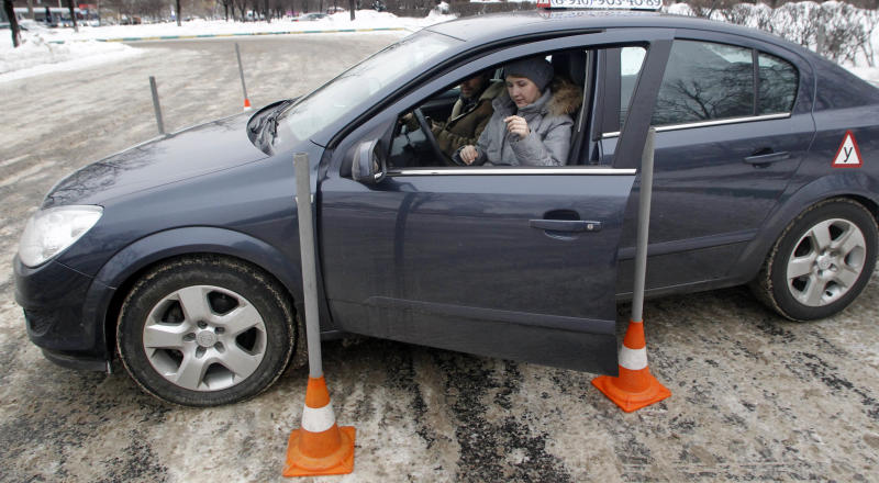 In this photo taken on Monday, Jan. 23, 2012, Natalya Veselova opens a door of her instructor's car at a driving training ground in the south-east of Moscow, Russia. For Veselova, applying for a driver's license has turned into a frustrating ordeal because she refuses to pay the customary bribe. (AP Photo/Mikhail Metzel)