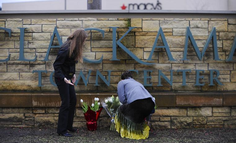 Leslie King, right and Tenille Beseda place flowers Wednesday Dec. 12, 2012, at the entrance to the scene of a multiple shooting yesterday at Clackamas Town Center Mall in Portland, Ore. A gunman who opened fire on shoppers at the mall had no connection to the two people he fatally shot and wanted to kill as many people as possible, police said Wednesday. (AP Photo/Greg Wahl-Stephens)