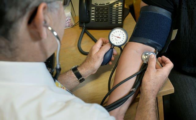 A GP checking a patient's blood pressure