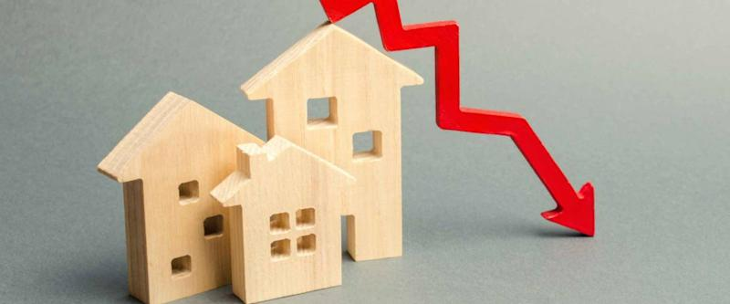 Miniature wooden houses and a red arrow down arrow, representing falling mortgage rates.