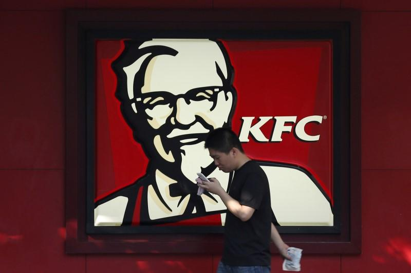 A man walks past a logo of KFC, outside a restaurant in Shanghai