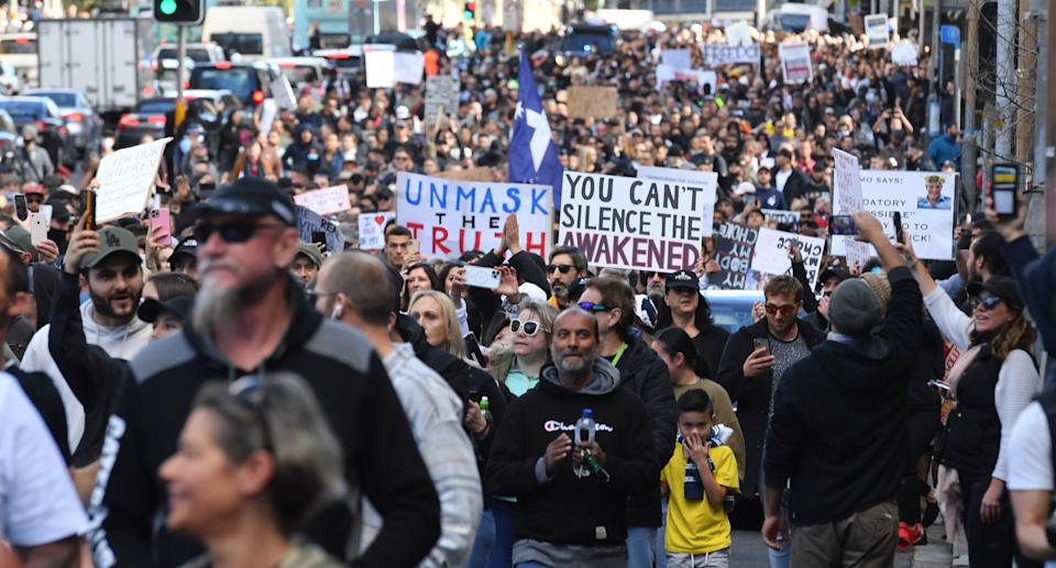 Protesters march along Broadway and George St towards Sydney Town Hall during the anti-lockdown rally at Hyde Park in Sydney on Saturday. Source: AAP