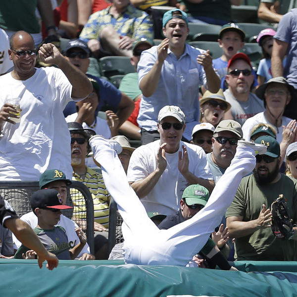 Fans cheer as Oakland Athletics third baseman Josh Donaldson dives into the crowd to make the catch on a foul ball hit by St. Louis Cardinals' Matt Carpenter in the fourth inning of a baseball game, Sunday, June 30, 2013, in Oakland, Calif. (AP Photo/Ben Margot)