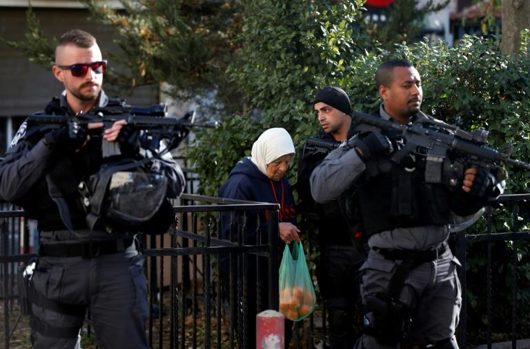 Israeli security forces stand guard as an elderly Palestinian woman walks past in Jerusalem