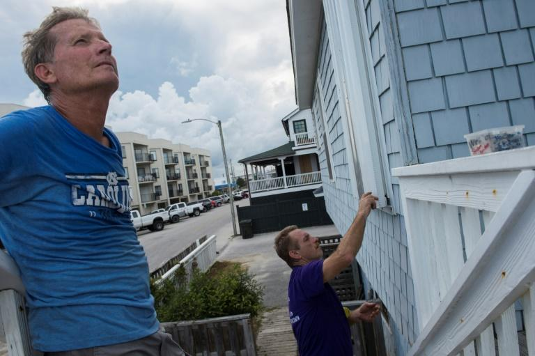 Ken Ripley (L) looks on as his friend Brian Calahan (C) seals a window on a beach house before the arrival of Hurricane Florence