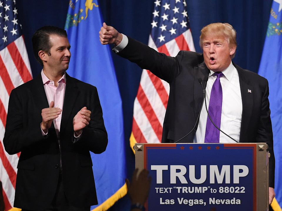 Donald Trump Jr. (L) looks on as his father, Republican presidential candidate Donald Trump, waves after speaking at a caucus night watch party at the Treasure Island Hotel & Casino on 23 February 2016 (Getty Images)