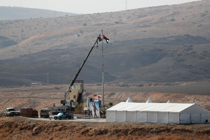 "Jordanian soldiers lower a Jordanian national flag near a tent at the ""Island of Peace"" in an area known as Naharayim in Hebrew and Baquora in Arabic, on the Jordanian side of the border with Israel, as seen from the Israeli side"