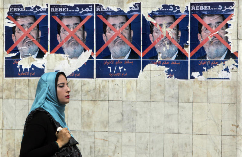 """An Egyptian walks past anti-government posters for a campaign calling for the ouster of Egyptian President Mohammed Morsi and for early presidential elections in Cairo, Egypt, Tuesday, June 11, 2013. Young activists are trying to rally public discontent with Egypt's Islamist President Morsi by fanning out in the streets and collecting millions of signatures on a petition calling for his removal. Morsi's Muslim Brotherhood has dismissed the campaign as irrelevant, even illegal, but the signature drive has stirred up Egypt's politics as the president nears the end of his tumultuous first year in office. The Arabic at the bottom of the poster reads, """"Down with the Muslim Brotherhood rule. June 30. At the presidential palace."""" (AP Photo/Amr Nabil)"""