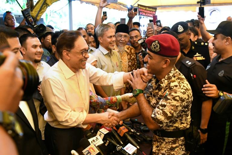 Anwar shakes hands with a prison officer as he speaks to the media following his release from hospital