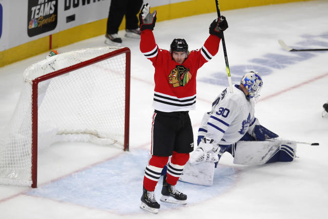 Chicago Blackhawks' Brandon Saad, left, celebrates his goal on Toronto Maple Leafs' Michael Hutchinson during the third period of an NHL hockey game Sunday, Nov. 10, 2019, in Chicago. (AP Photo/Jim Young)