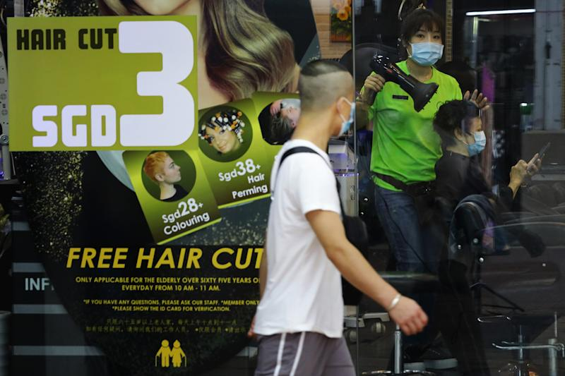 SINGAPORE - APRIL 05: A hairdresser wearing protective mask attends to a customer on April 5, 2020 in Singapore. The Singapore government will be closing non-essential workplaces and schools temporarily for a month from April 7 to contain the spread of the COVID-19 infection. The Ministry of Health reported 120 new cases on April 5, the largest daily increase since the outbreak in January, bringing the country's total to 1309. (Photo by Suhaimi Abdullah/Getty Images)