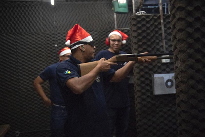 Santa's helpers -- or rather instructors the Colt 45 Shooting Club in Rio de Janeiro -- prepare weapons for their students (AFP Photo/Mauro Pimentel)
