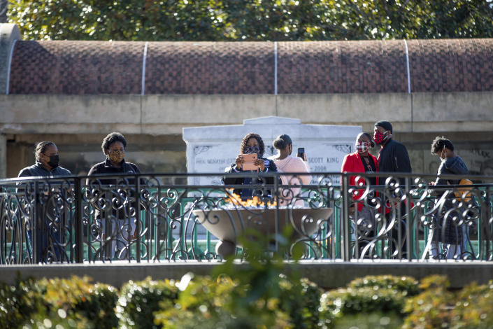 People visit the eternal flame at the tomb of Rev. Martin Luther King Jr. and his wife Coretta Scott King on Monday, Jan. 18, 2021, to celebrate the Martin Luther King Jr. holiday, in Atlanta. (AP Photo/Branden Camp)