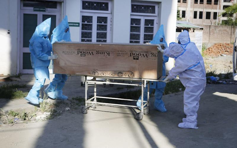 Ambulance drivers in protective gear carry the coffin of a woman who died from coronavirus - Farooq Khan/Shutterstock