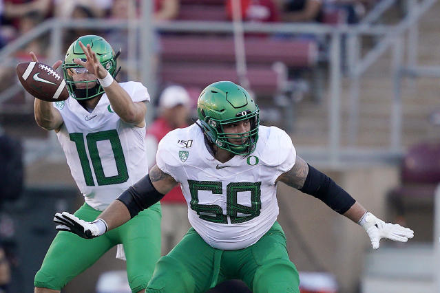 FILE - In this Sept. 21, 2019, file photo, Oregon offensive linemen Shane Lemieux blocks for quarterback Justin Herbert (10) during the first half of an NCAA college football game against Stanford in Stanford, Calif. The New York Giants selected Lemieux in the fifth round of the NFL football draft on Saturday, April 25, 2020. (AP Photo/Tony Avelar, File)