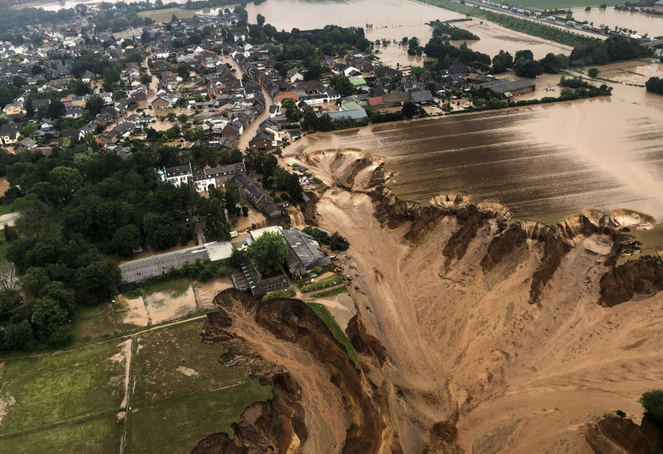 This image provided on Friday, July 16, 2021 by the Cologne district government shows the Blessem district of Erftstadt in Germany. Rescuers were rushing Friday to help people trapped in their homes in the town of Erftstadt, southwest of Cologne. Regional authorities said several people had died after their houses collapsed due to subsidence, and aerial pictures showed what appeared to be a massive sinkhole. (Rhein-Erft-Kreis via AP)