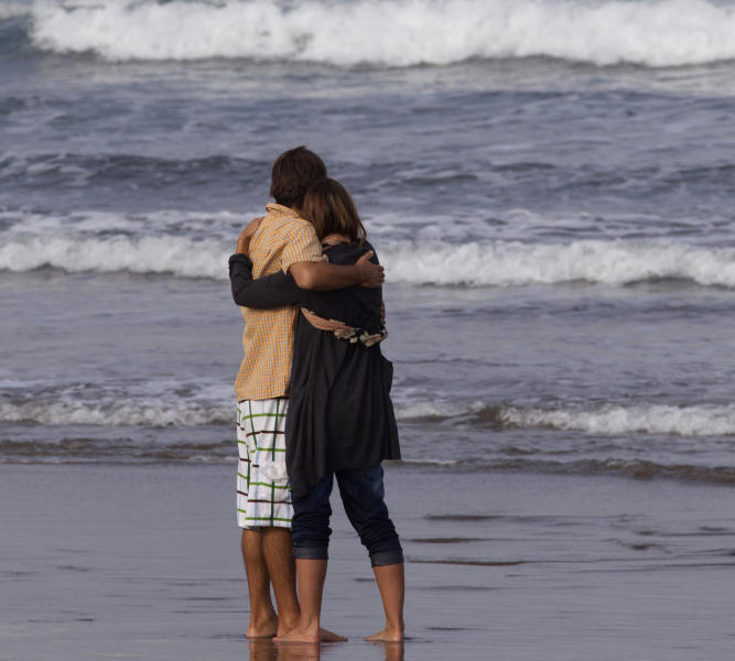Meg Strange, right, wife of Adam Strange is comforted by friend Simon Shephard, as people gather on Muriwai Beach near Auckland, New Zealand, Thursday, Feb. 28, 2013, to say goodbye to Adam Strange. About 150 friends and family of Adam, 46, wrote messages to him in the sand and stepped into the water Thursday at a New Zealand beach to say goodbye after he was killed Wednesday by a large shark. (AP Photo/New Zealand Herald, Brett Phibbs) New Zealand Out, Australia Out